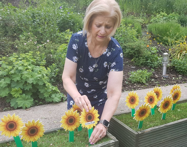 Mary Pomfret - Planting a sunflower in memory of her husband